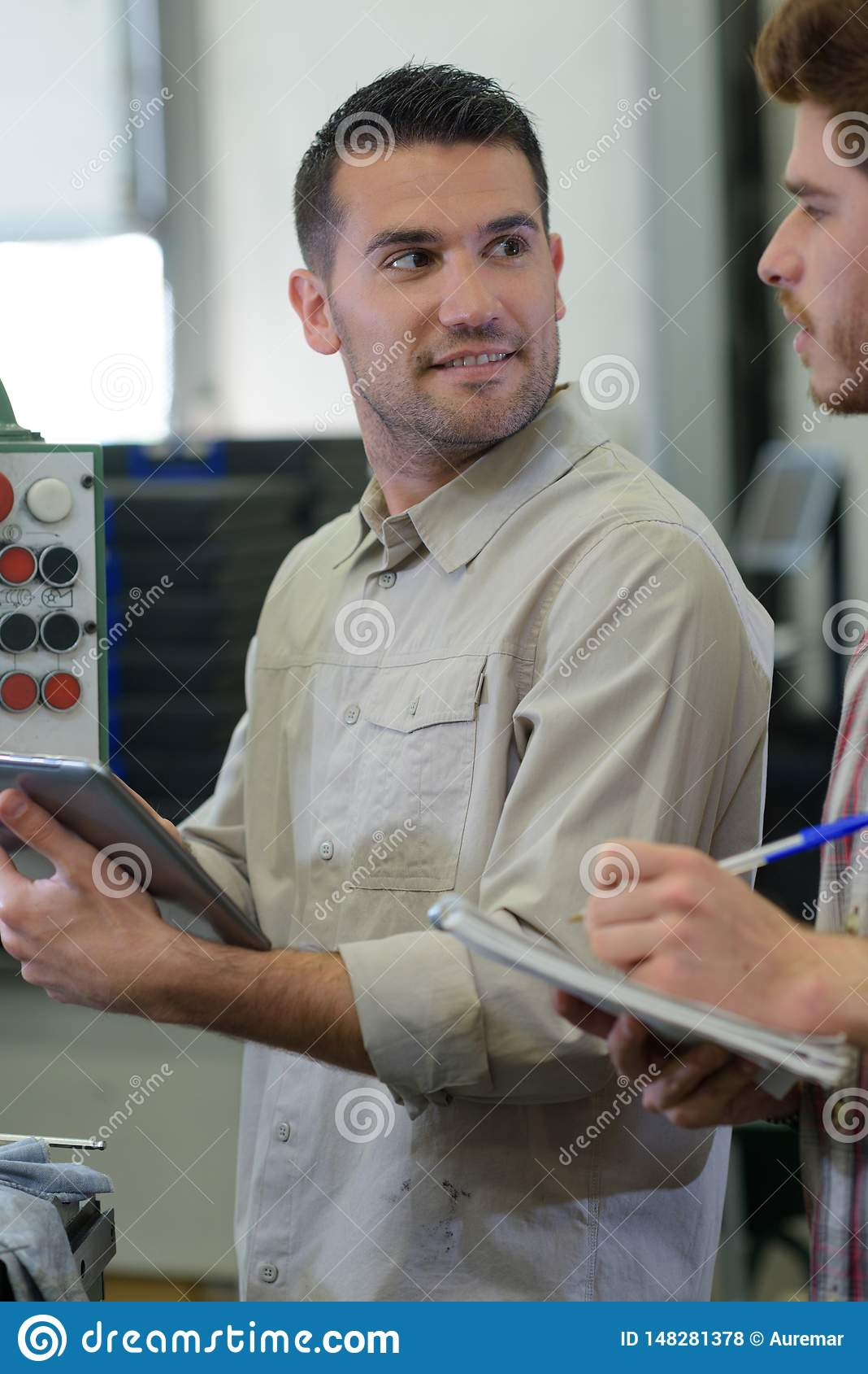 Portrait man working at modern factory operating machine