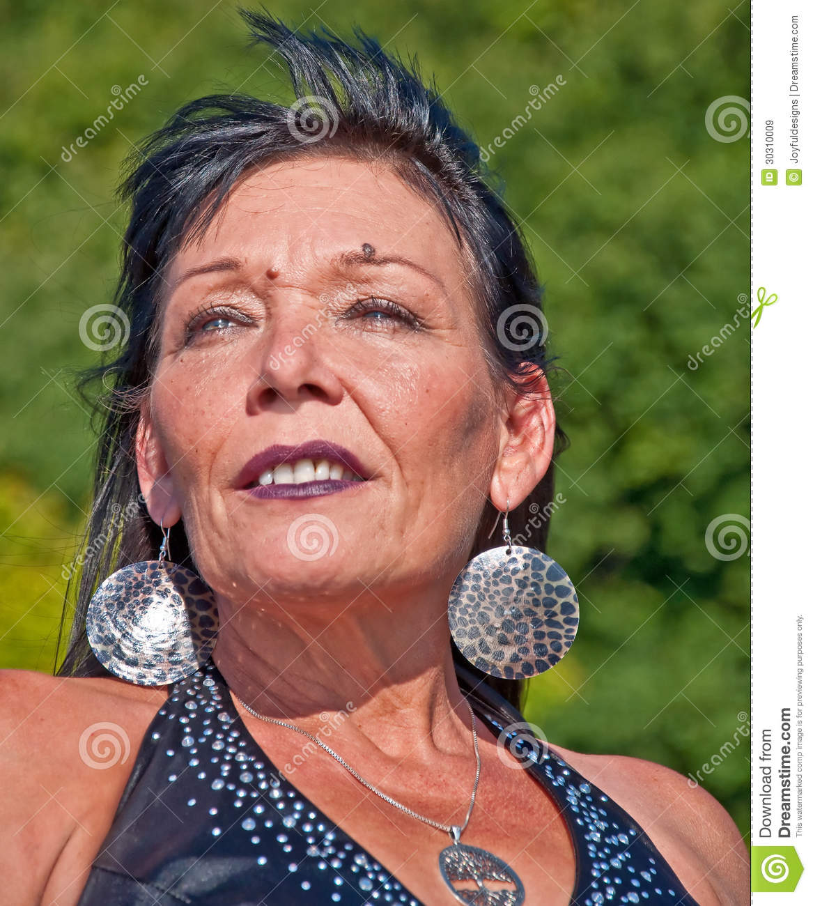 This is a portrait of a mature woman of Native American descent in an ...