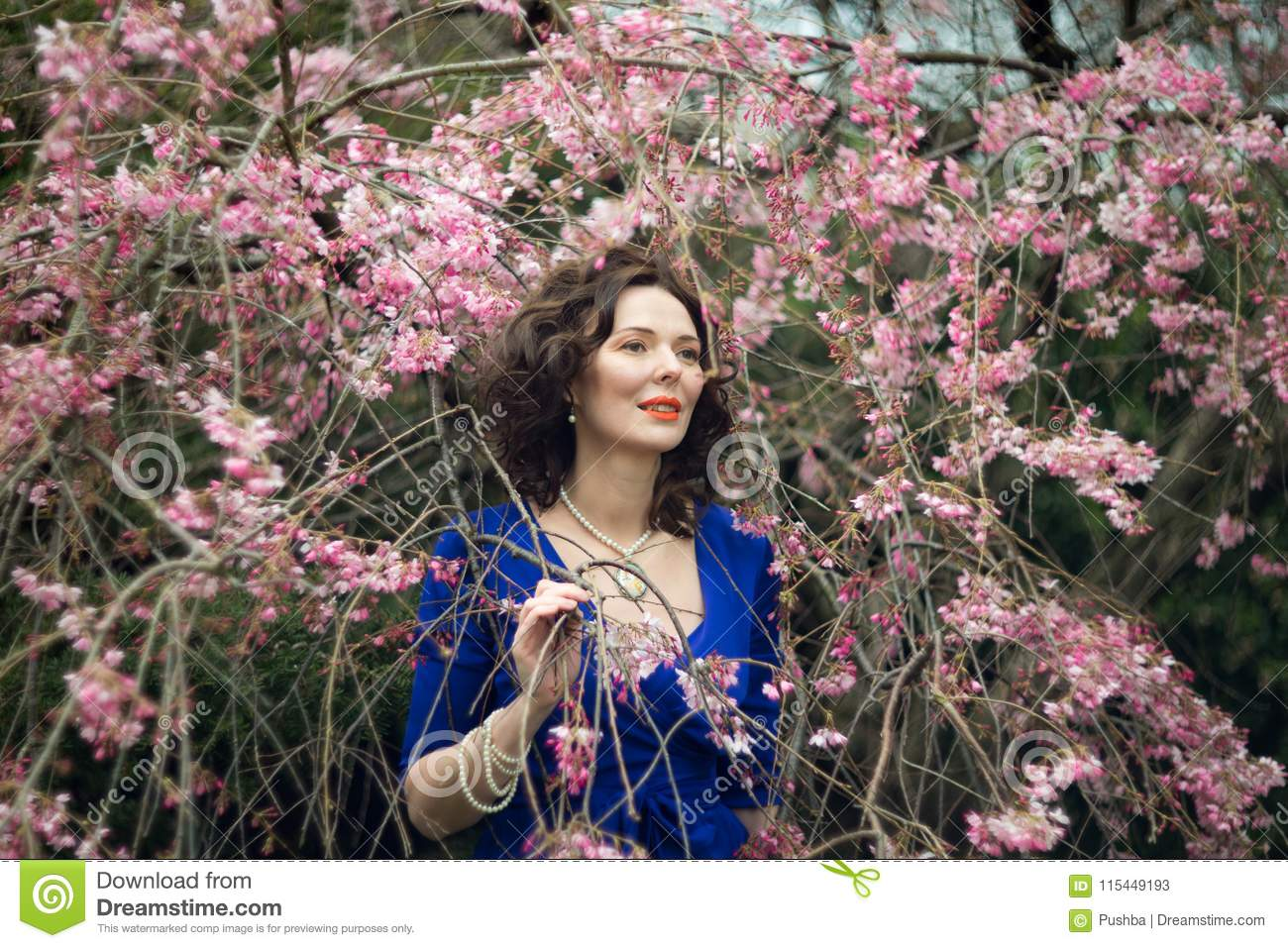 Portrait of a middle-aged brunette in a blue dress next to a cherry blossom