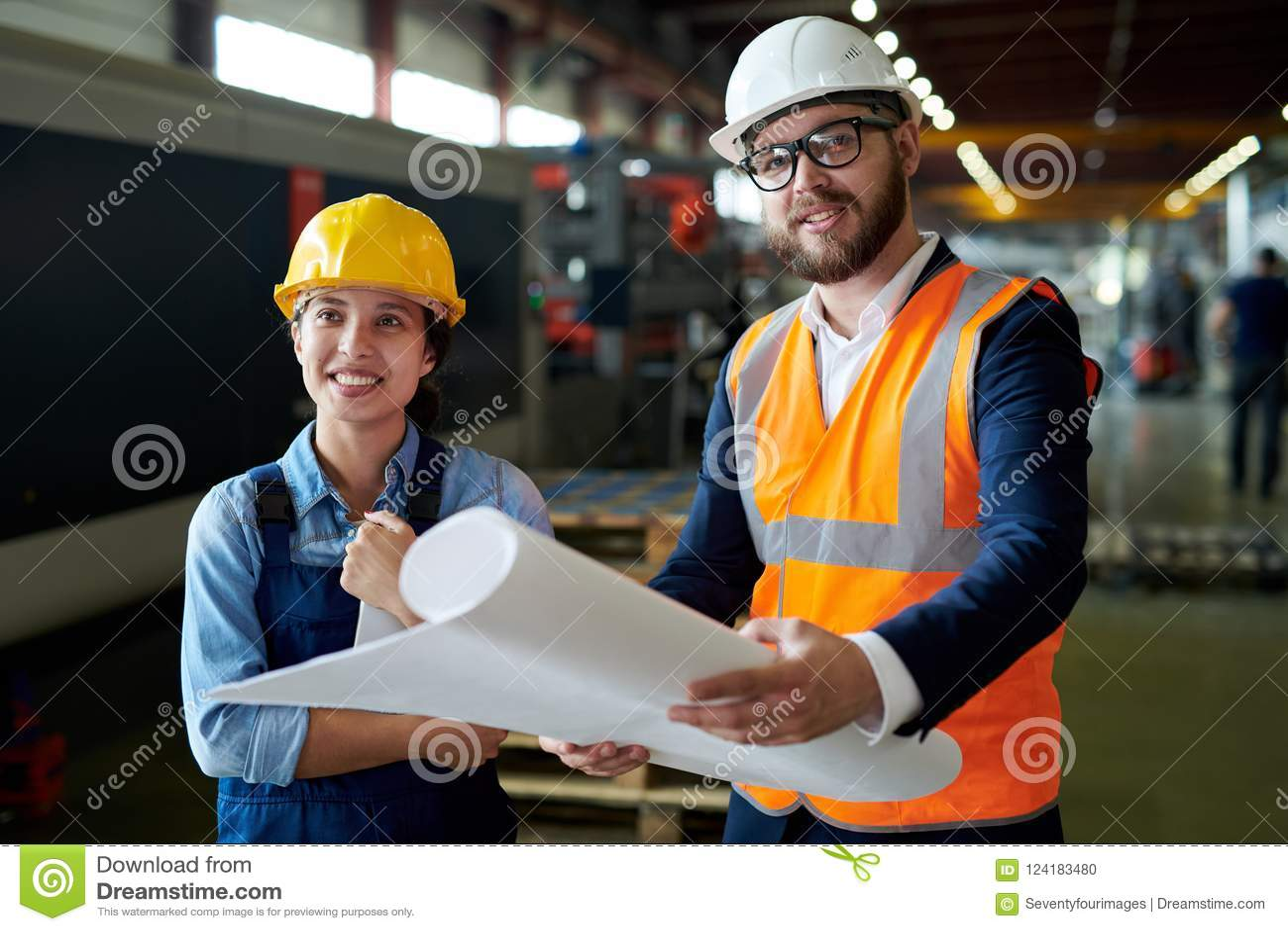 Smiling Engineers Holding Blueprints