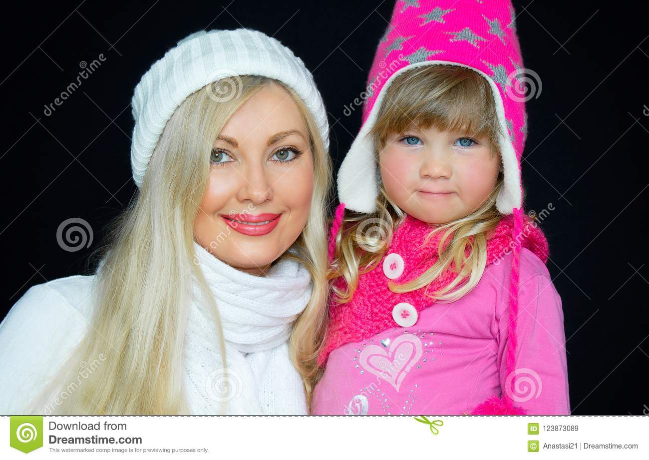 Portrait. Mom and daughter, in knitted hats, on a black background. Happy family, smiles and joy.