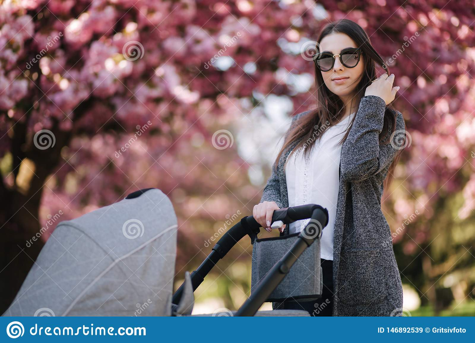 Portrait of mom stand with stroller in the park. Happy young mother walking with baby. Background of pink tree