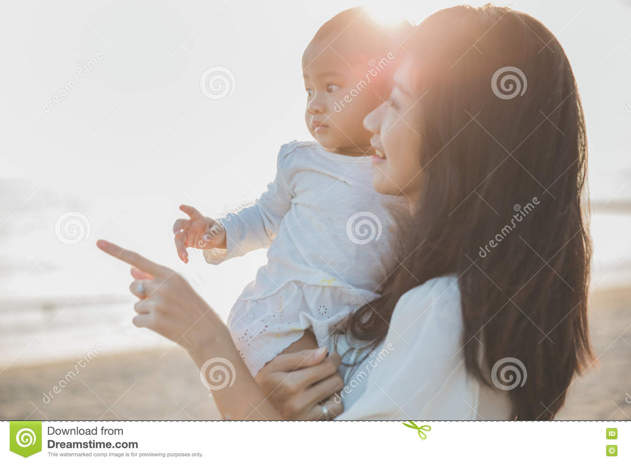 Portrait of mother and baby in the beach at sunset