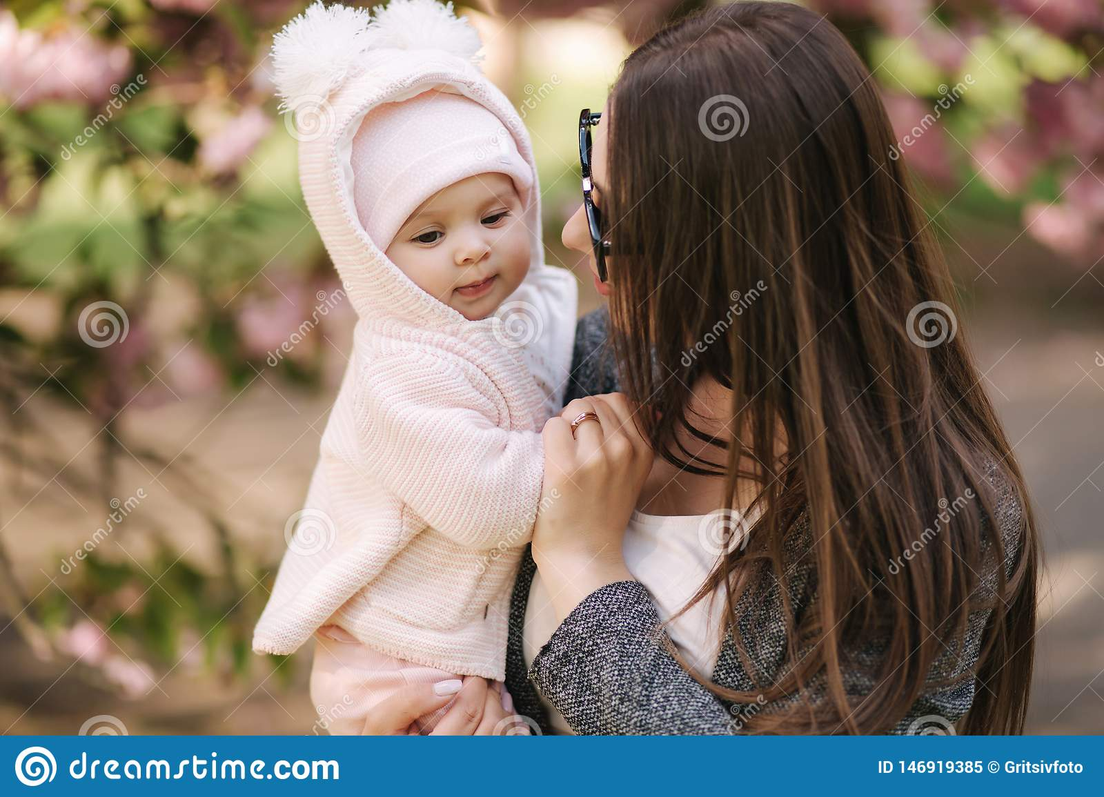 Portrait of mother and her little baby girl. Beautiful mom and cute baby. Mother hud her daughter. Baby dressed in