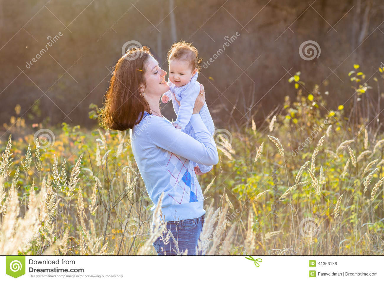 Portrait of mother with her new born baby in sunny park