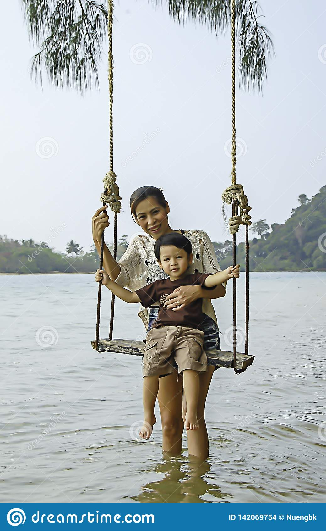 Portrait of mother and son playing swing chair in the sea