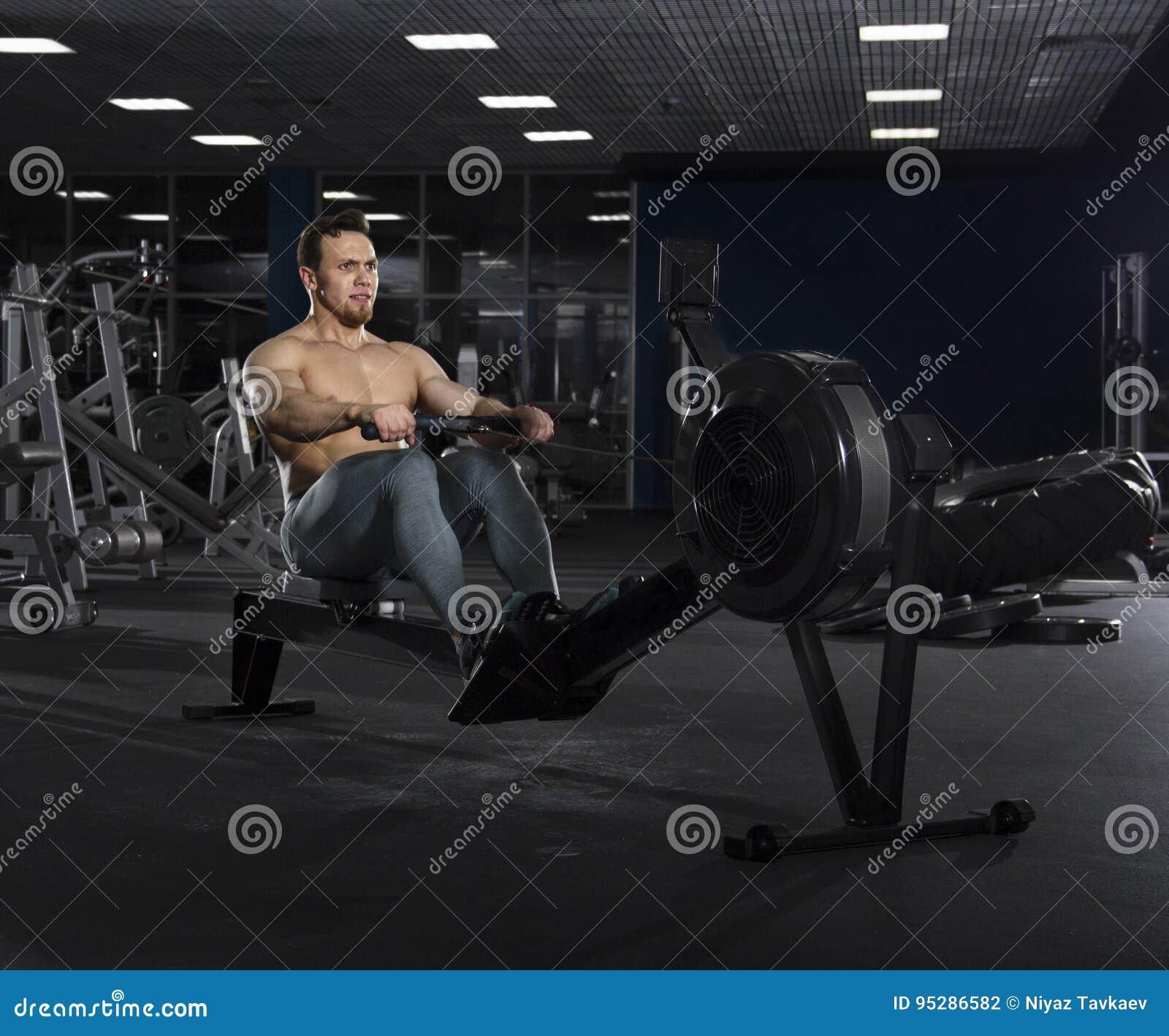 Portrait of muscular athlete working on rowing machine in modern