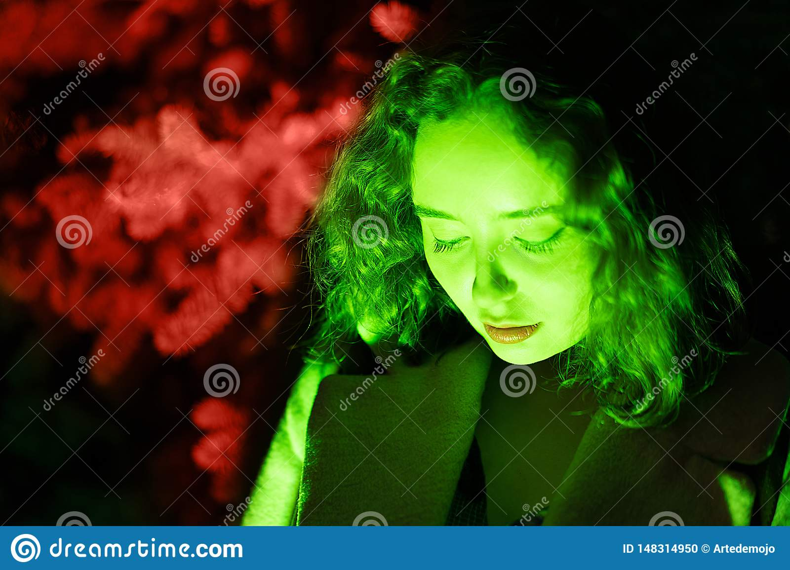 Portrait of a mysterious woman in green lighting with coral background