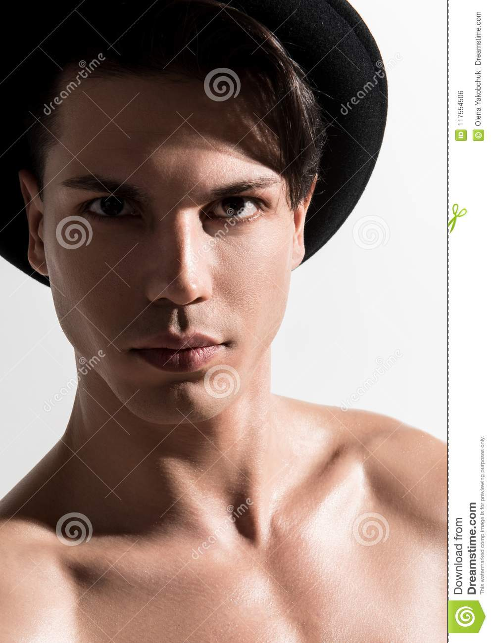 Portrait of naked young male with clean and healthy skin in stylish hat is  standing against light background and looking at camera decisively.