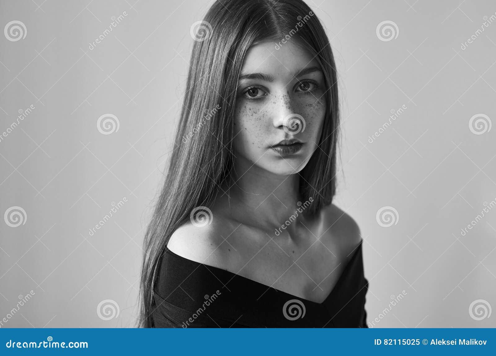 Portrait noir et blanc dramatique d une belle fille seule avec des taches de rousseur d isolement sur un fond blanc dans le tir d