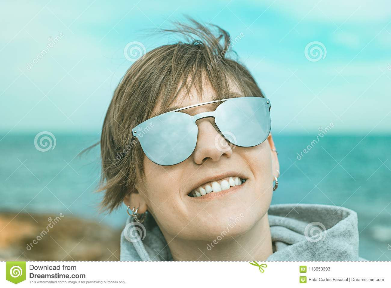 Portrait of a normal girl with smiling sunglasses on the beach.