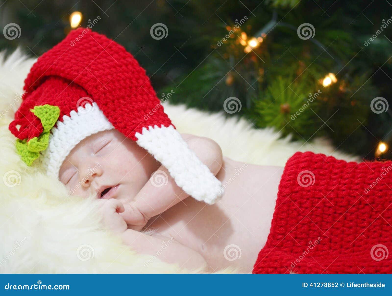 Portrait nouveau-né de bébé dormant dans le costume de knit de Noël sur la couverture blanche de fourrure