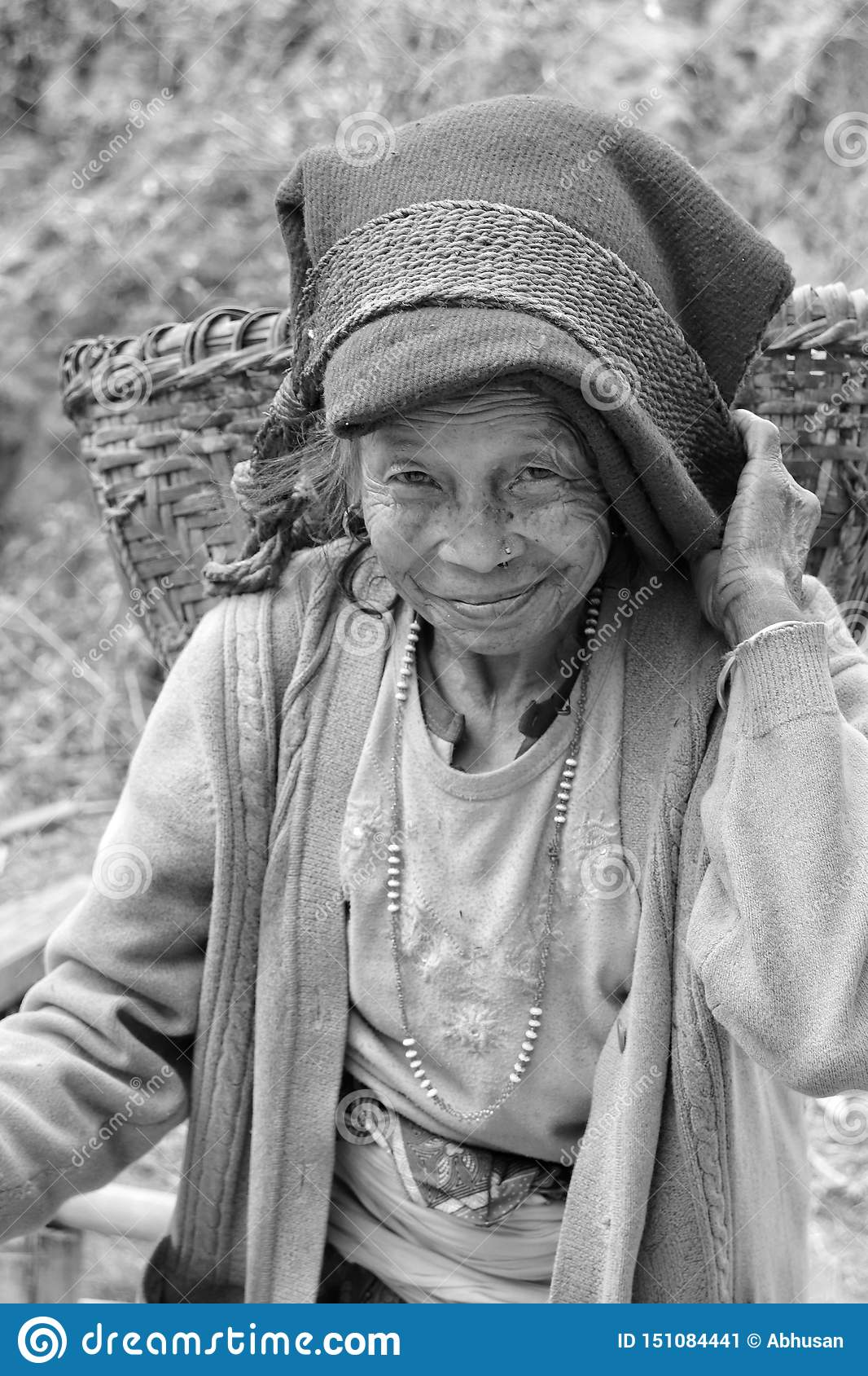 Portrait of an old woman with beautiful smile carrying doko