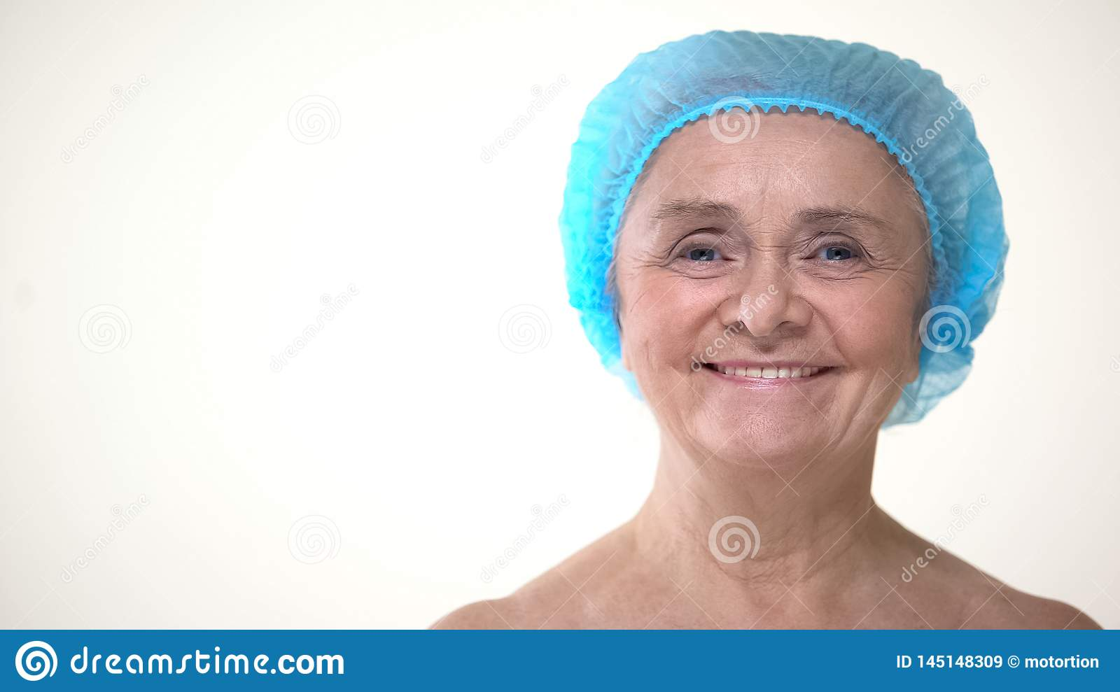 Portrait of old woman in hygienic cap before plastic surgery, cosmetology