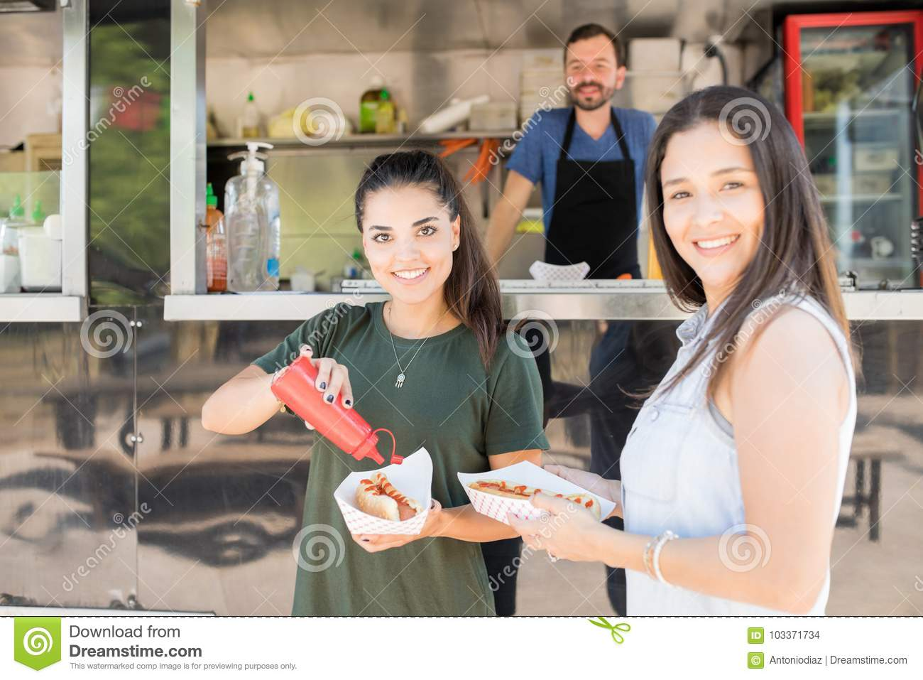 Happy girls eating at a food truck