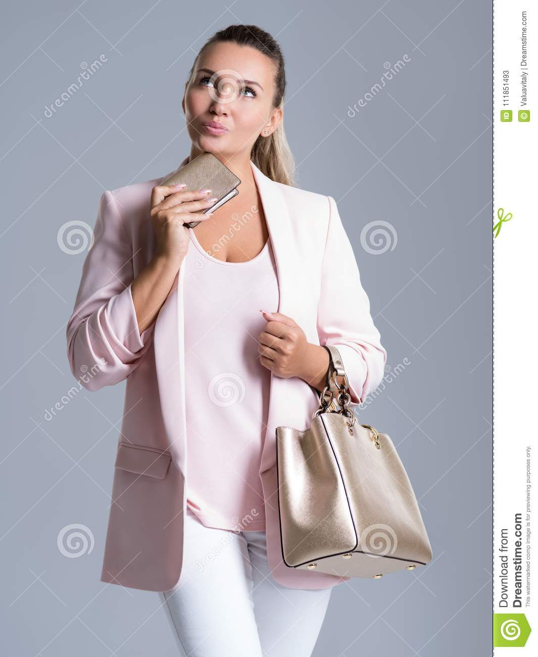 Portrait of pensive woman with purse in hand and a handbag in ha