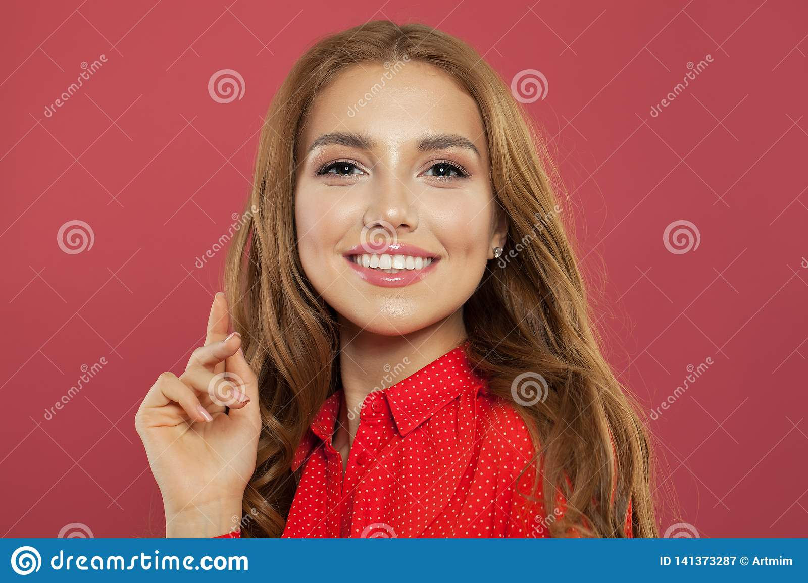 Portrait of perfect young woman on coral pink background. Beautiful pretty girl smiling and having fun. Positive emotions,