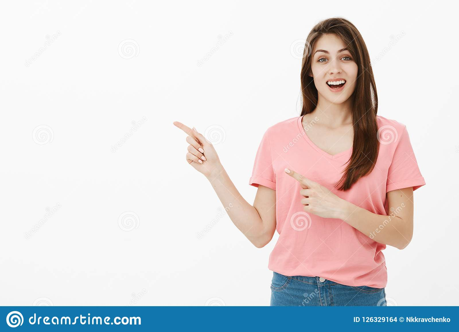 Portrait of pleased carefree happy girlfriend in casual clothes, smiling joyfully and pointing at upper left corner