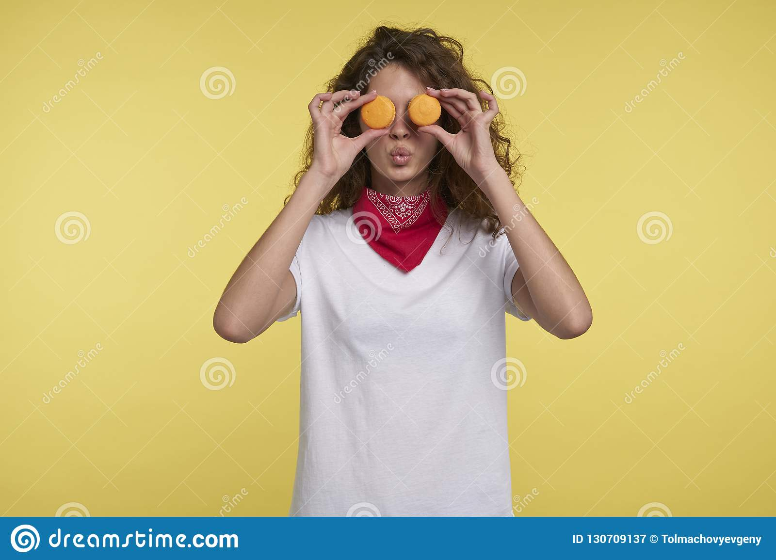 A portrait of pretty brunette italian woman and macarons over yellow background