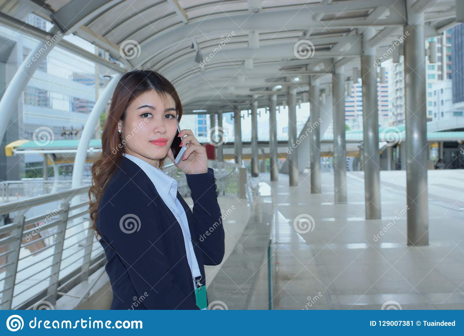 Portrait of pretty face young Asian business woman talking on phone at urban city background.