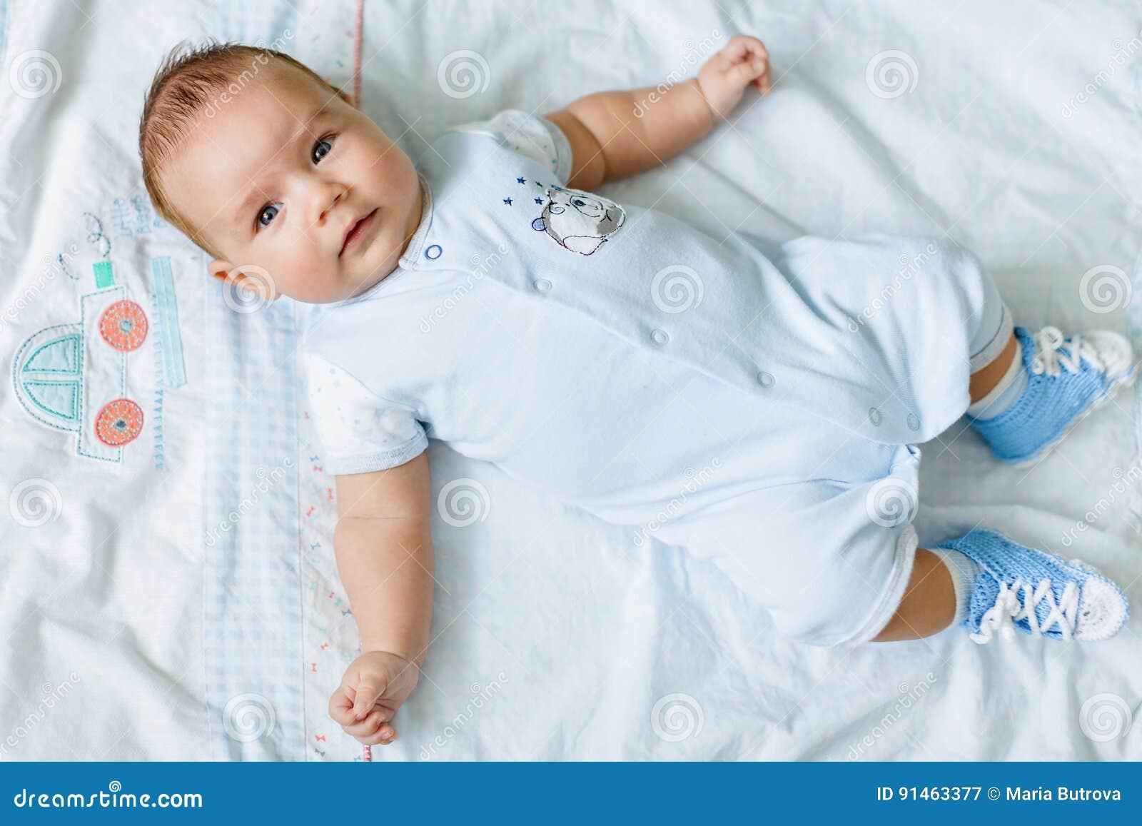 Portrait of a pretty little baby , lying on a light blanket