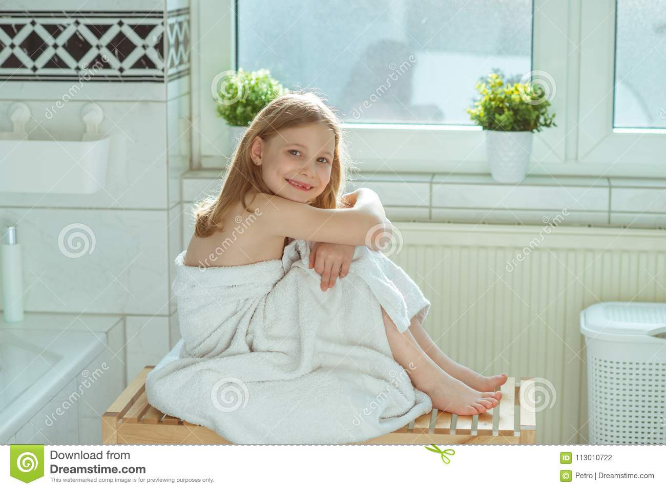 Portrait of pretty little child girl with white towel after show