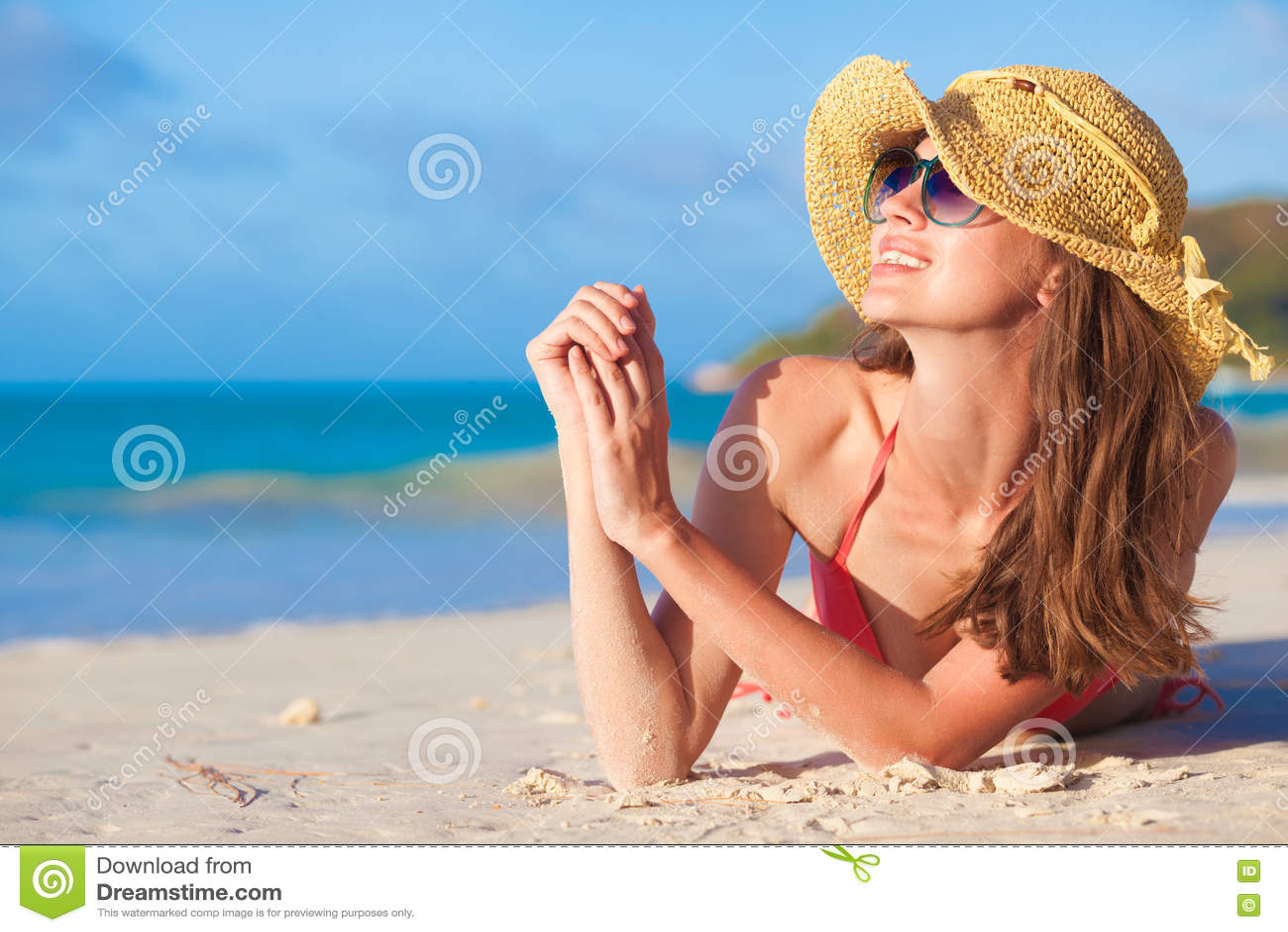 Portrait of pretty long haired woman in bikini having fun at tropical beach. Praslin, Seychelles