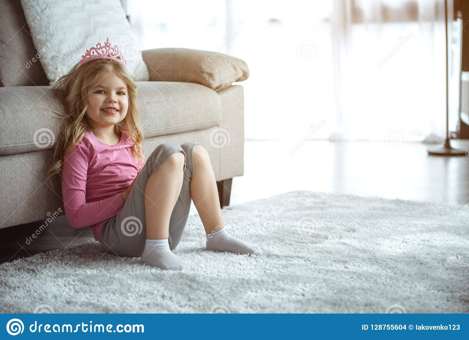 Friendly little girl sitting on floor near couch