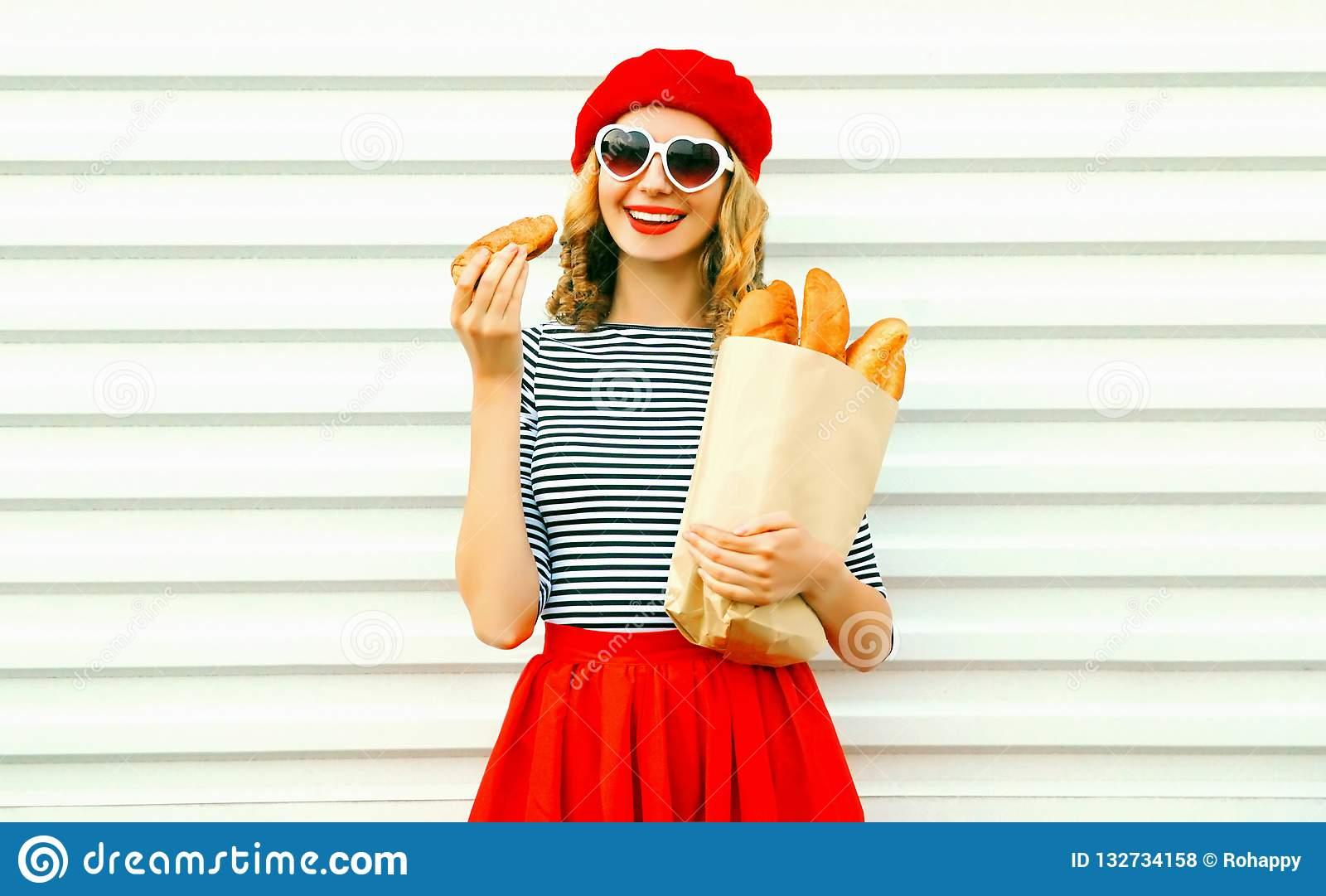 e62e15686 Portrait pretty smiling young woman wearing red beret holding croissant,  paper bag with long white bread baguette on white wall background