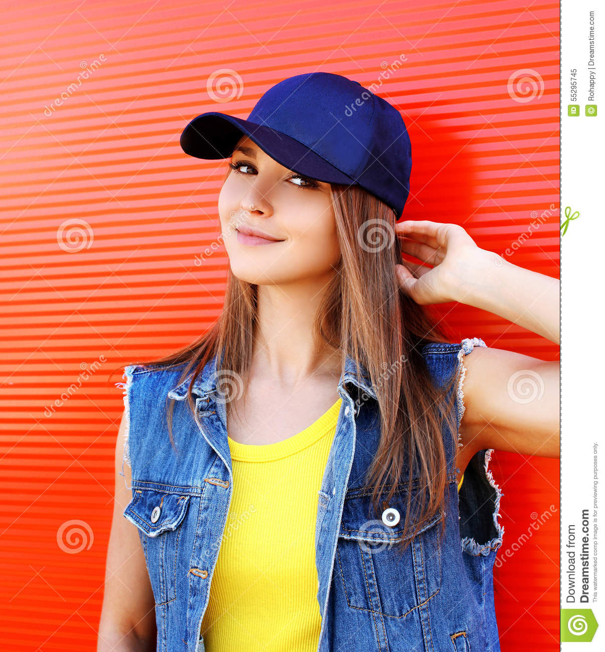 Portrait of pretty stylish young girl wearing a cap and jeans clothes over  red background 38c97556faa6