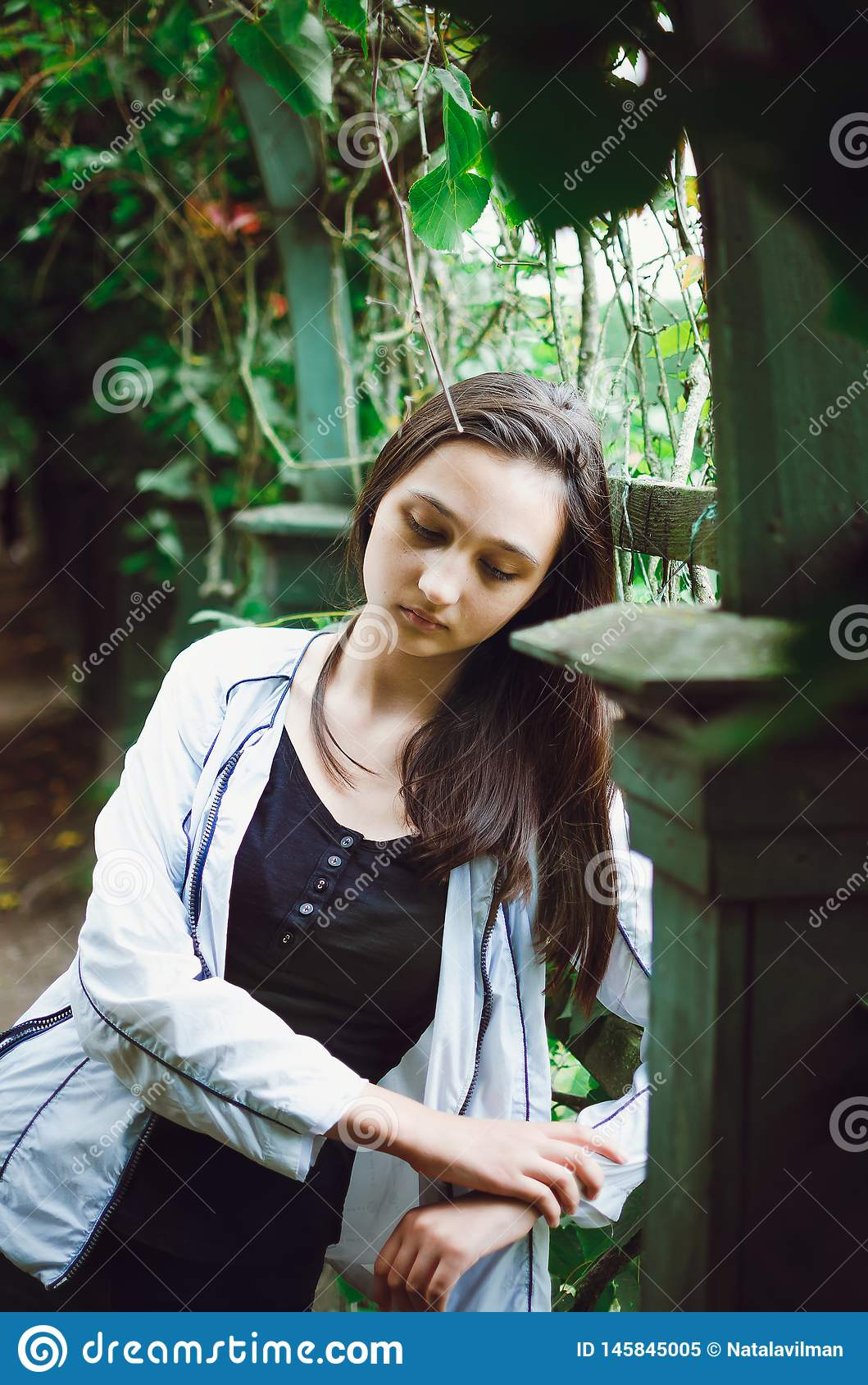 Portrait of a pretty teen girl on a background of nature. Vertical photo