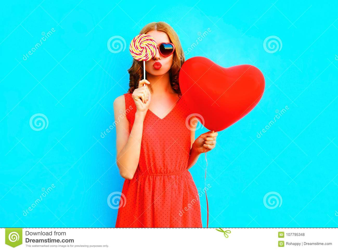 Portrait pretty woman with a lollipop candy, air balloon on blue