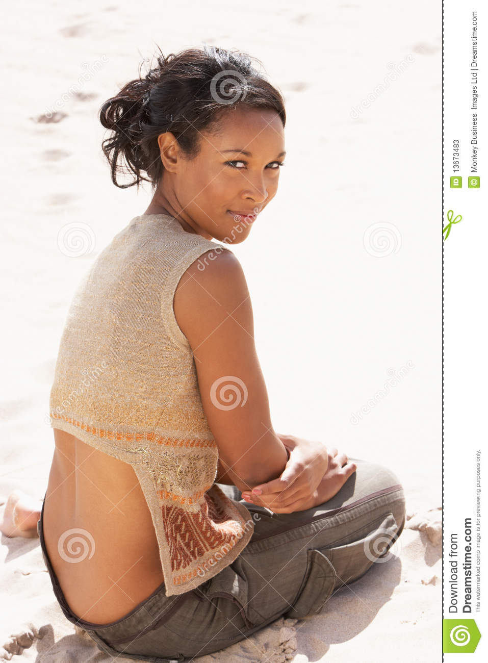 Portrait Of Pretty Young Woman Sitting On Beach
