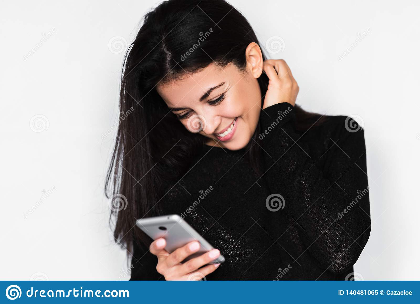 Portrait in profile of attractive young happy woman using smart phone with healthy toothy smile