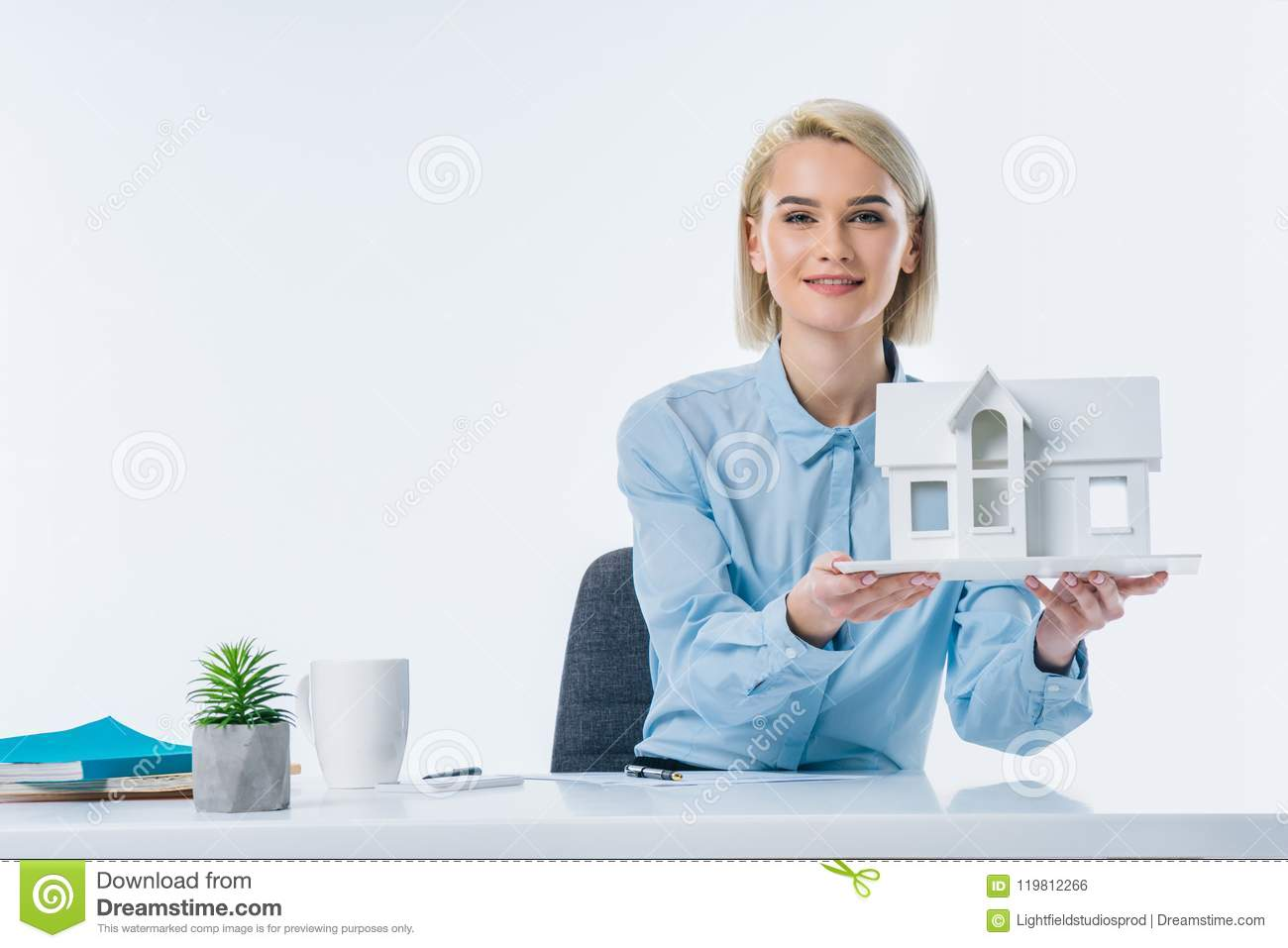 portrait of real estate agent showing house model