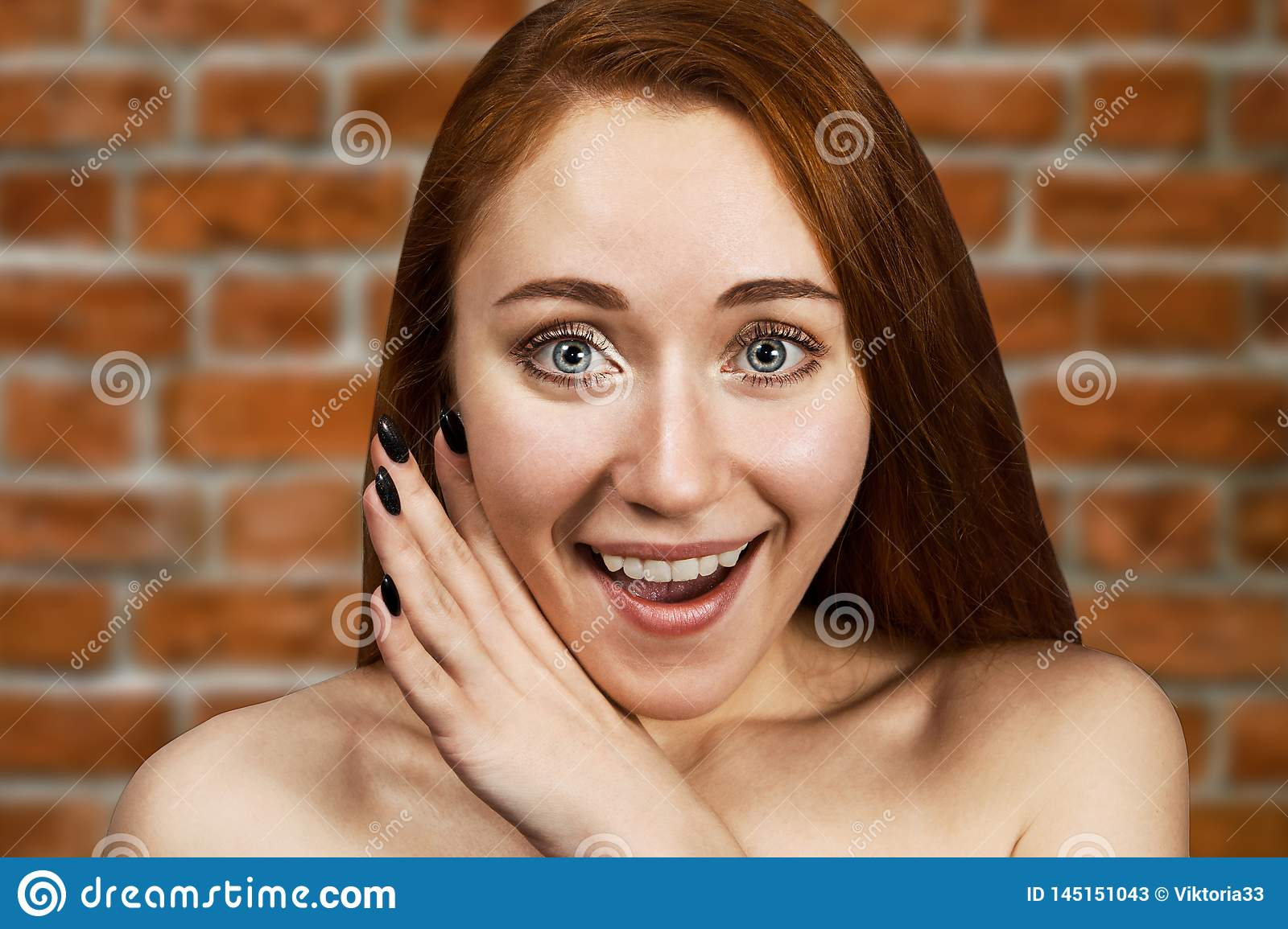 Portrait of a redhead young girl sharing a secret and gossip with her mouth open