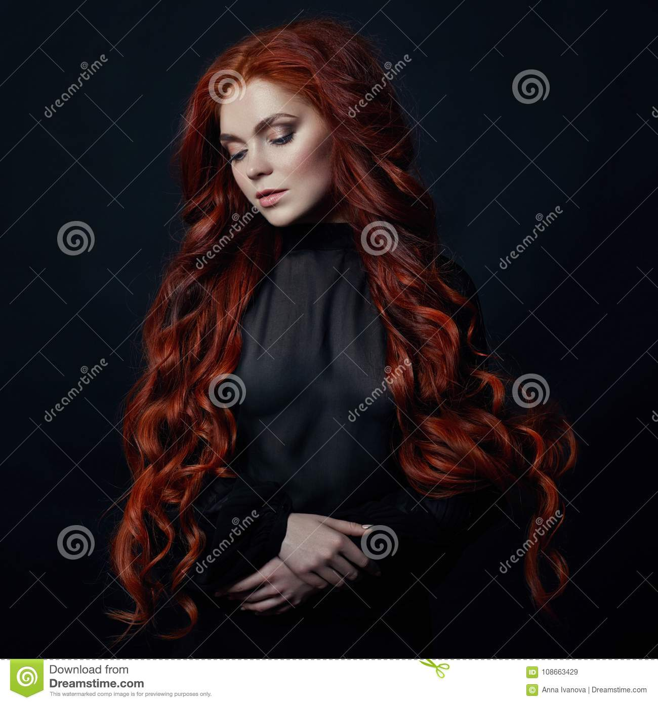 Portrait of redhead woman with long hair on black backgroun