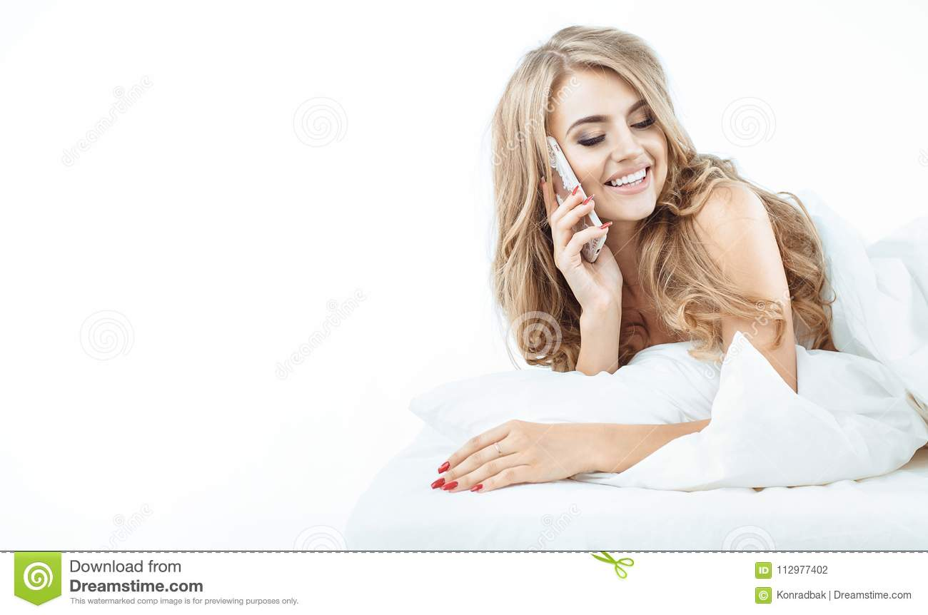 Portrait of a relaxed blonde using a smartphone