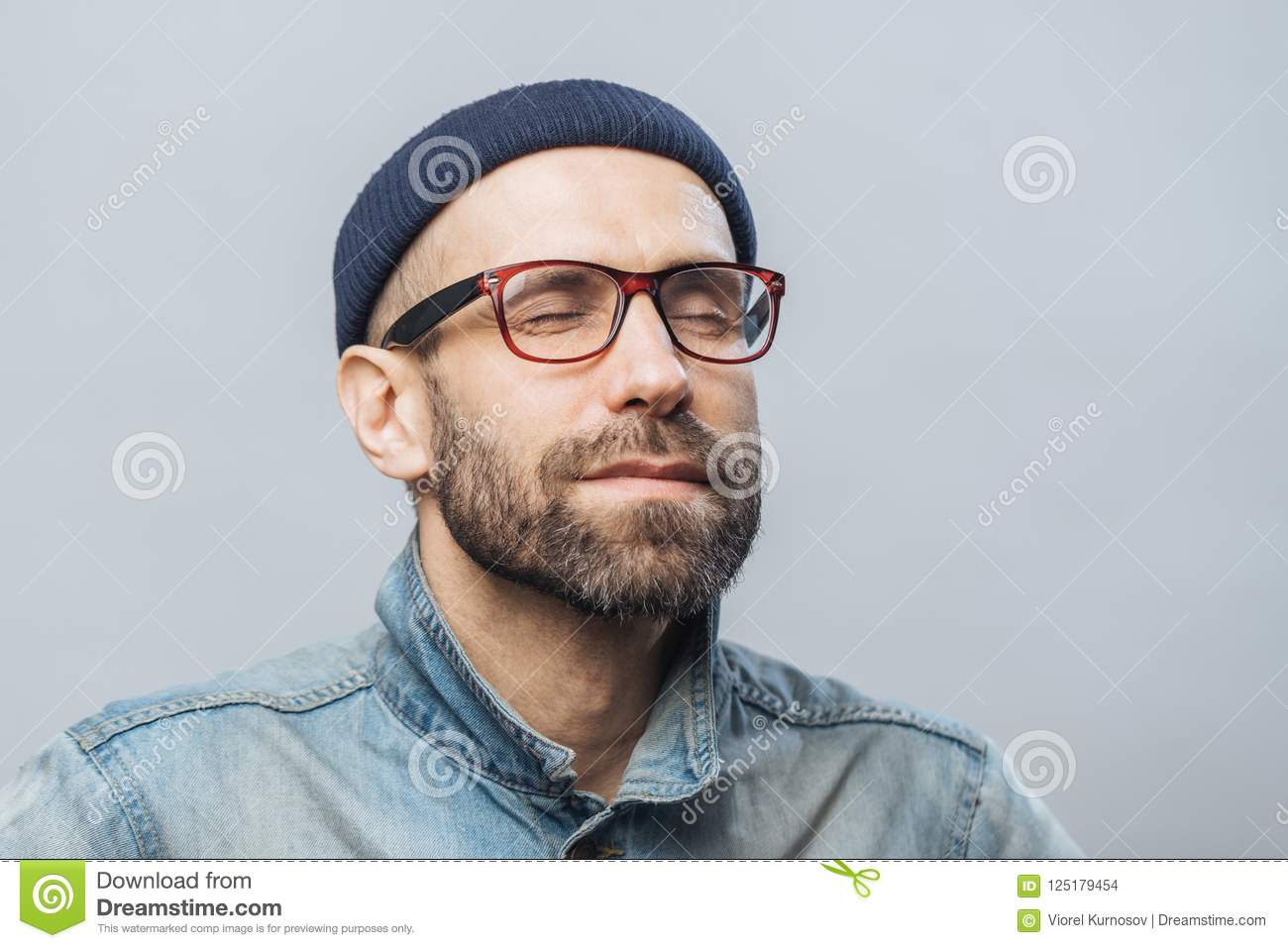 Portrait of relaxed unshaven male with closed eyes wears glasses, keeps eyes closed, enjoys calm atmosphere, isolated over white b