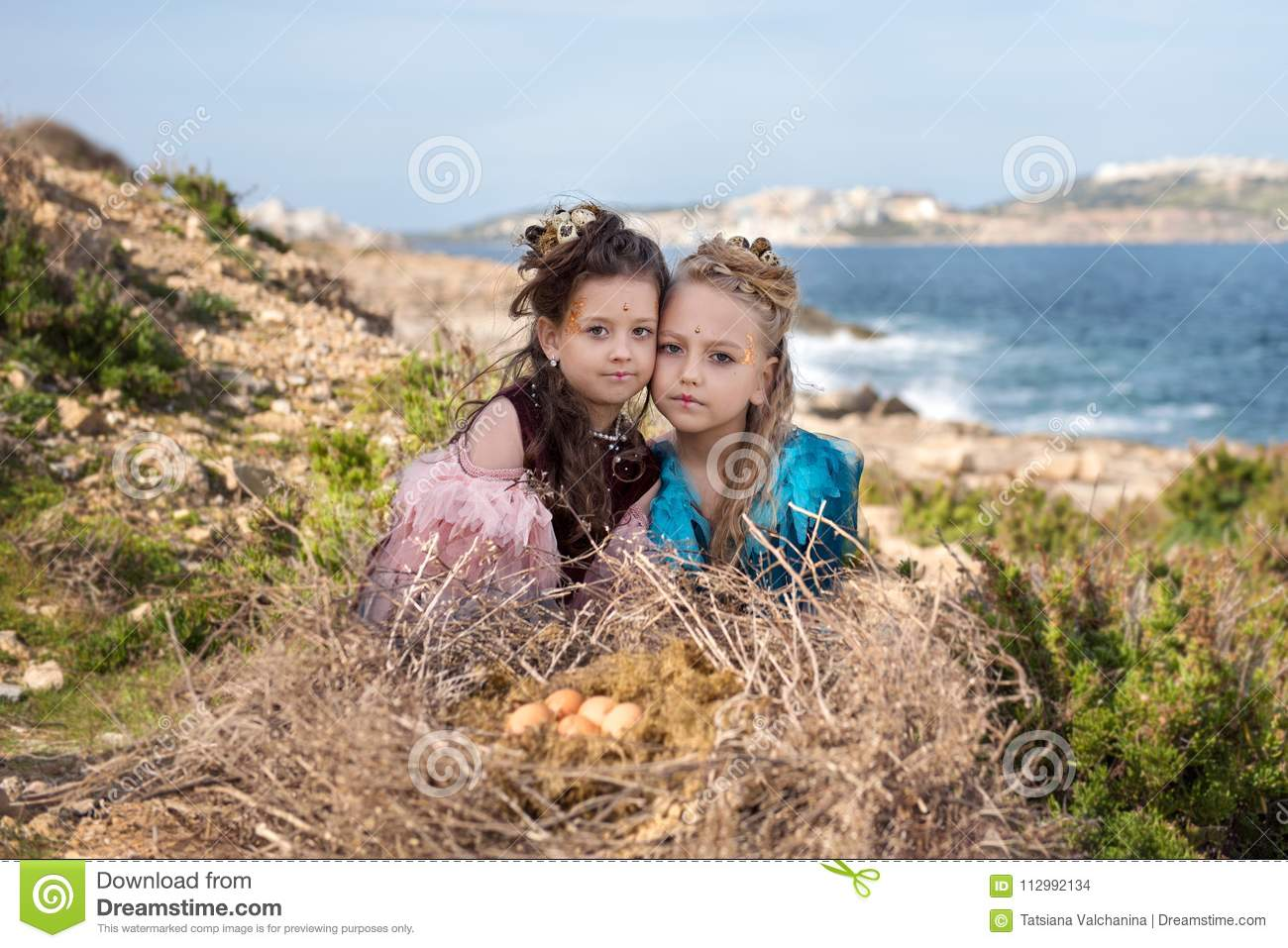 Portrait of a religious Easter play with two girls in suits of birds sitting near a huge nest with eggs