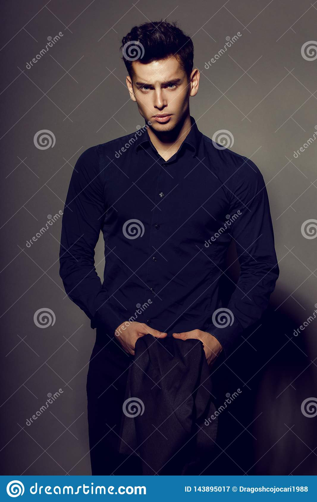 Portrait of rich, sexy brunette man in black suit posing on camera, isolated on grey background