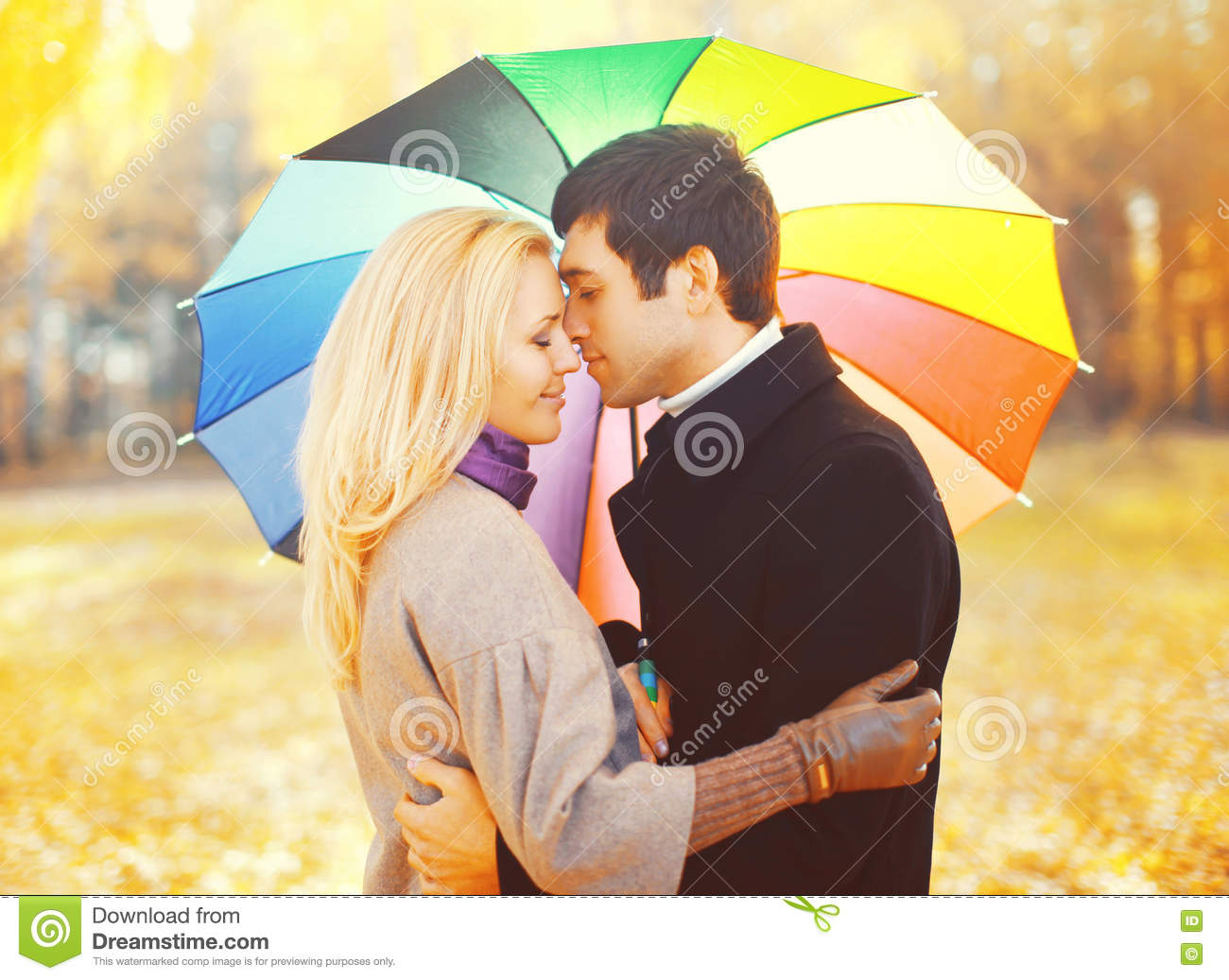 Portrait of romantic kissing couple in love with colorful umbrella together at warm sunny day over yellow leafs
