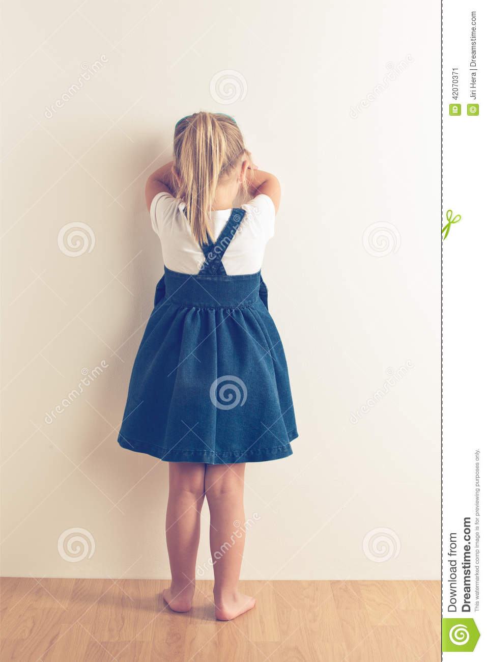portrait of sad little girl standing near wall stock photo