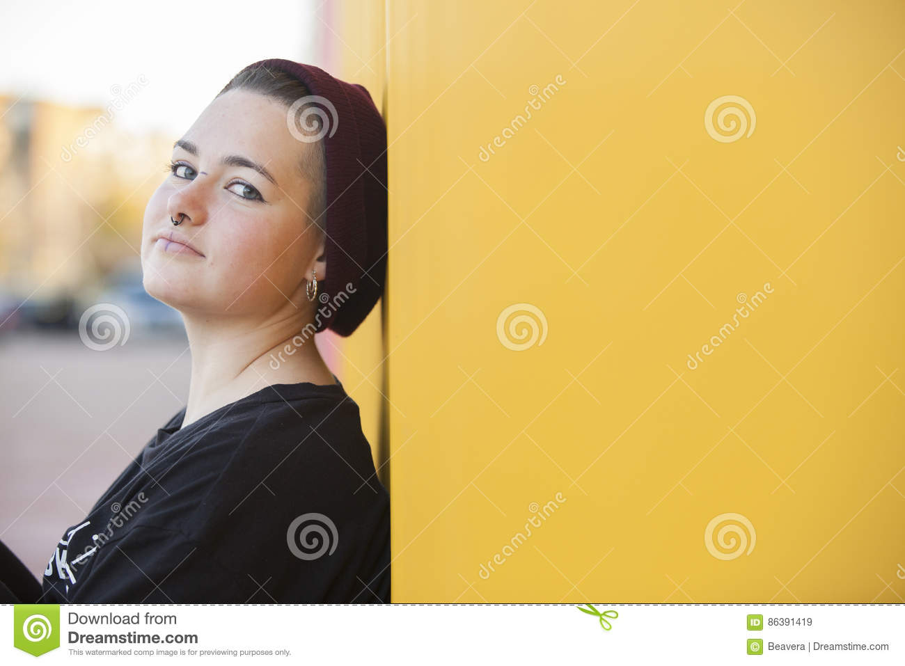 Portrait of a sad teen gay woman on a yellow wall