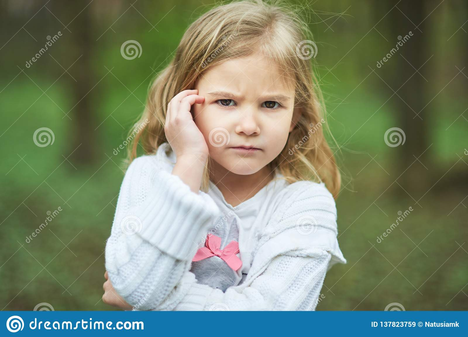 Portrait of sad unhappy little girl. Little sad child is lonesome. upset and distraught angry facial expression.