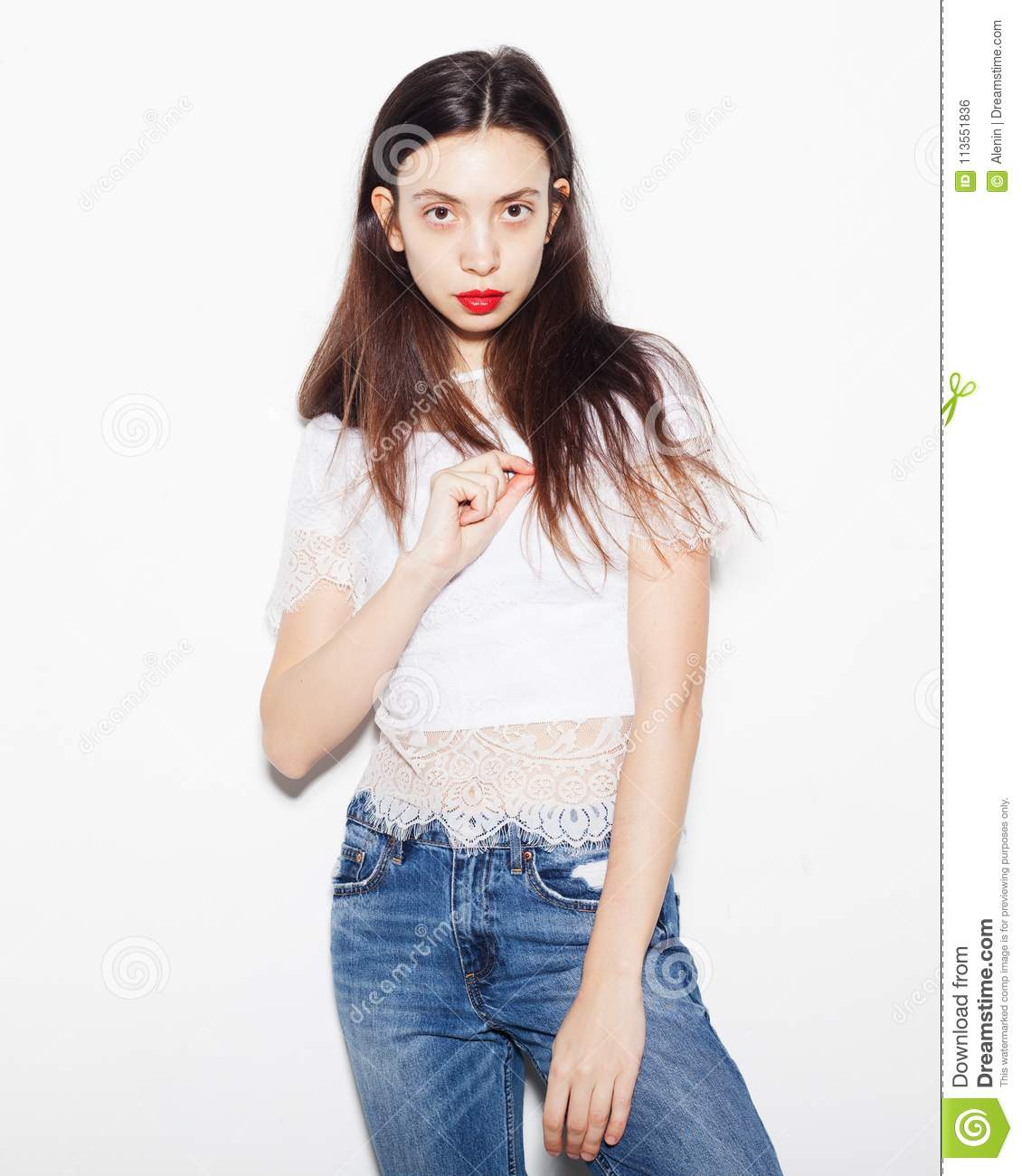 Portrait Of A Sad Young Woman In Top And Jeans Posing In The Studio