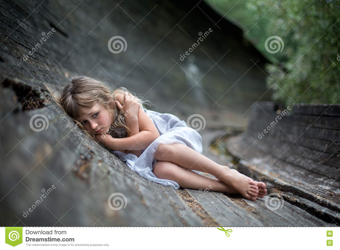 Portrait of scared little girl in forest