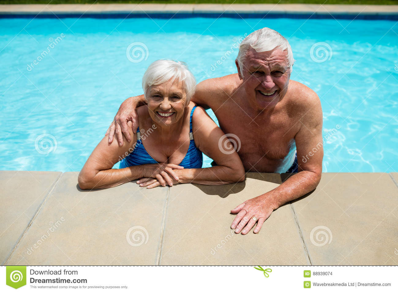 Portrait of senior couple relaxing together in pool