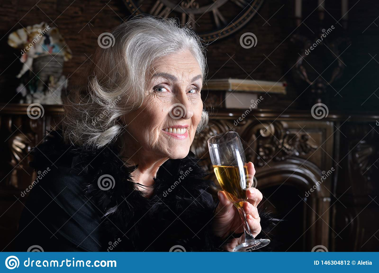 Close up portrait of senior smiling woman with champagne