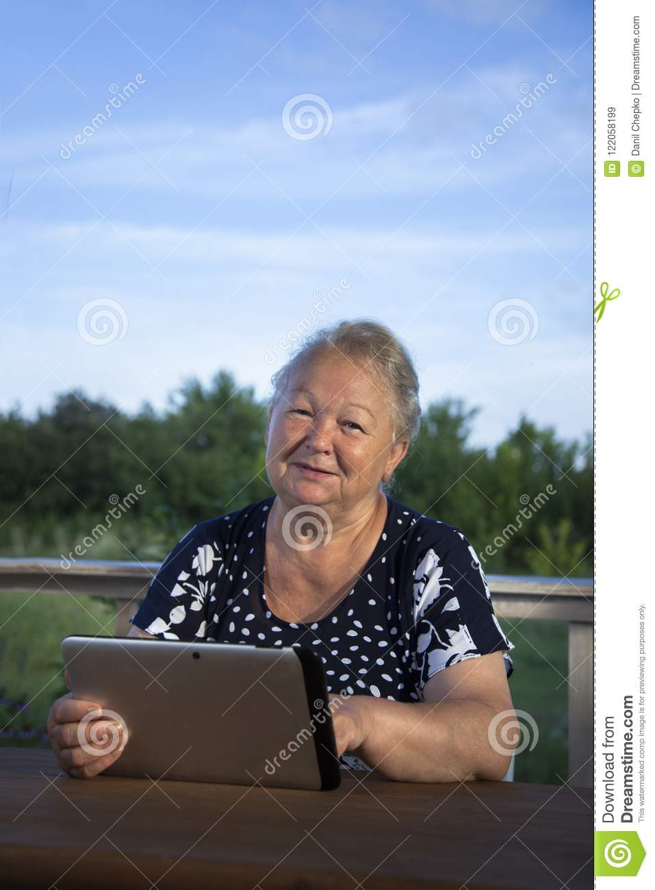 Portrait of senior woman with tablet computer on veranda outdoor